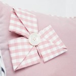 A photo of a gingham bow sewn onto a cushion
