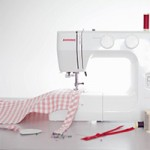 A photo of a sewing machine taken side-on with some checked fabric