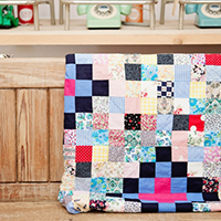 A photo of a patchwork quilt hanging over a bench