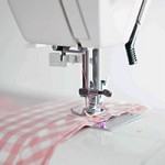 A photo of a sewing machine with some gingham fabric