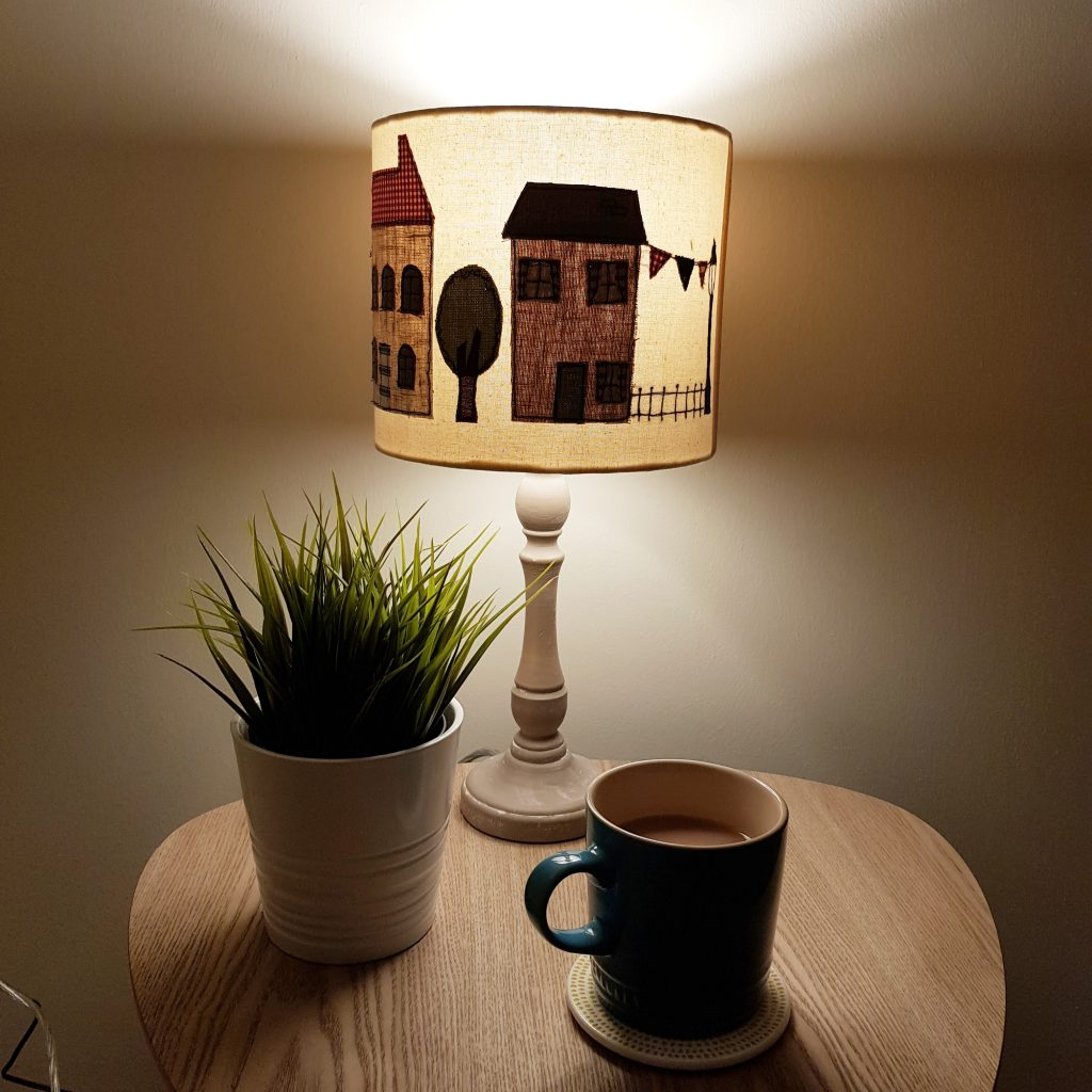 Table lamp on side table with tea and plant