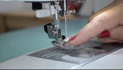 finger pointing at sewing machine needle